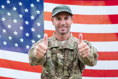 up: Soldier looking at camera thumbs up against an american flag