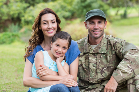 family with one child: Handsome soldier reunited with family on a sunny day
