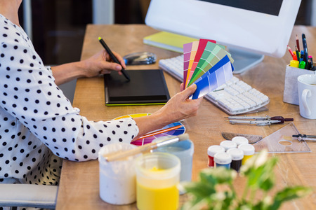 creating: Casual businesswoman looking at colour swatch and drawing with digitizer in the office Stock Photo