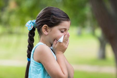 enfant malade: Petite fille soufflant son nez sur une journée ensoleillée Banque d'images