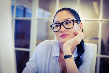 bored woman: Bored woman sitting at her desk in creative office Stock Photo