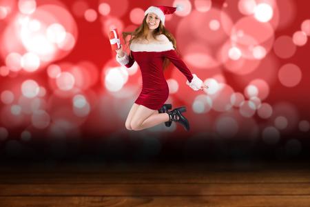 pere noel sexy: Rousse Festive sauter avec cadeau contre la conception de lumi�re chatoyante sur planches