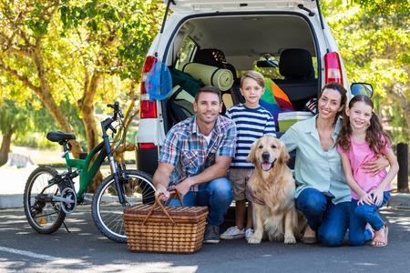 rodzina: Szczęśliwa rodzina przygotowuje się do podróży drogi w słoneczny dzień