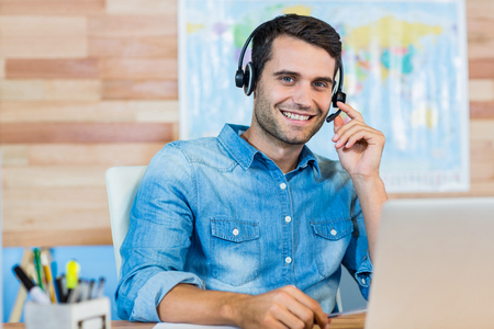 travel agent: Handsome travel agent smiling at camera in the office Stock Photo
