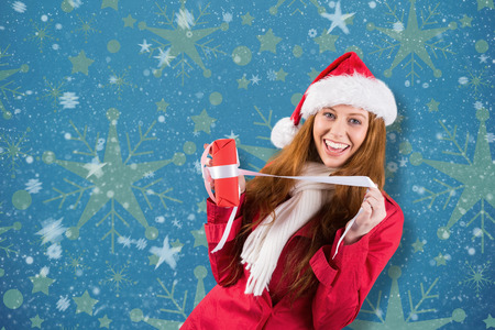 unwrapping: Festive redhead opening a gift against snowflake wallpaper pattern