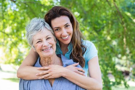 vrouwen: moeder en grootmoeder smilling in een park op een zonnige dag Stockfoto