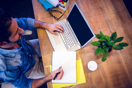 computer writing: Designer working at his desk in creative office Stock Photo