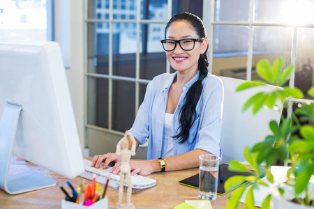 Smiling casual businesswoman working on computer in the office Stock Photo