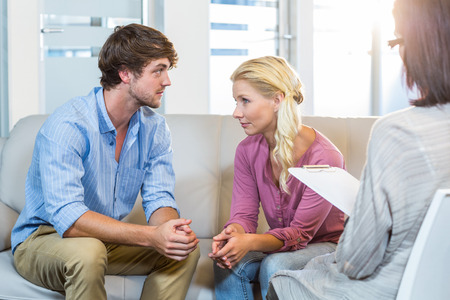 desolaci�n: Unsmiling couple talking with their therapist in the office