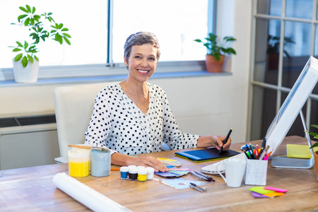 digitizer: Casual businesswoman looking at colour swatch and drawing with digitizer in the office Stock Photo