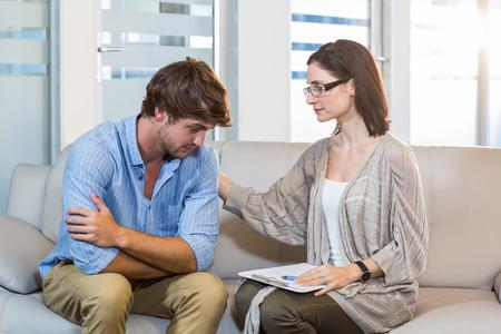 sicologia: Psicólogo consolar a un paciente deprimido en la oficina