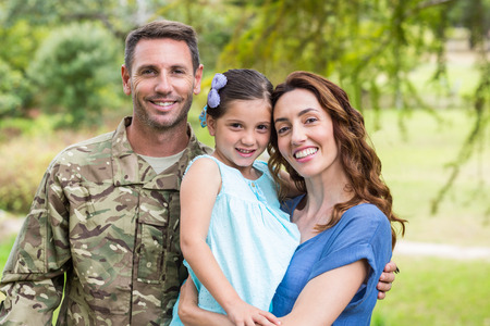family park: Handsome soldier reunited with family on a sunny day