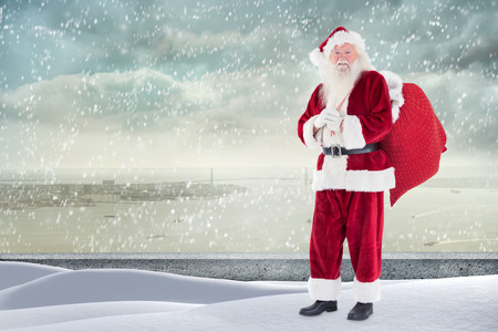 ledge: Santa standing on snowy ledge against coastline city