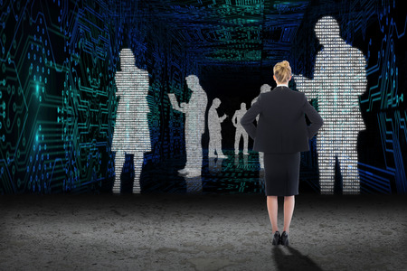 data matrix: Businesswoman standing with hands on hips against business people in data matrix