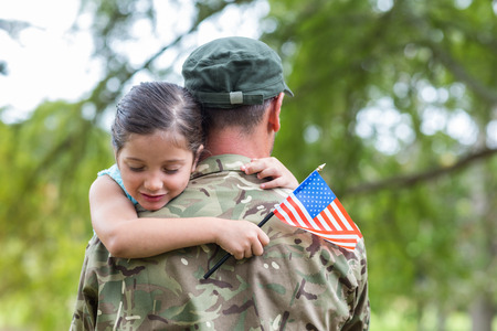 military uniform: Soldier reunited with his daughter on a sunny day Stock Photo