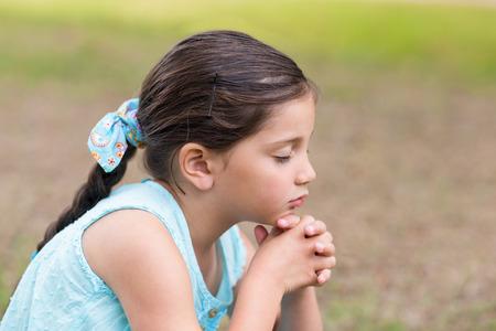 manos orando: La niña diciendo sus oraciones en un día soleado Foto de archivo