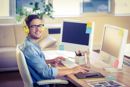 Happy designer smiling at camera in creative office
