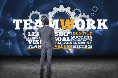 buzzwords: Thinking businessman against teamwork buzzwords with cogs and wheels Stock Photo