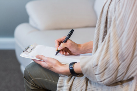Psychologist sitting on the couch and taking notes in the office