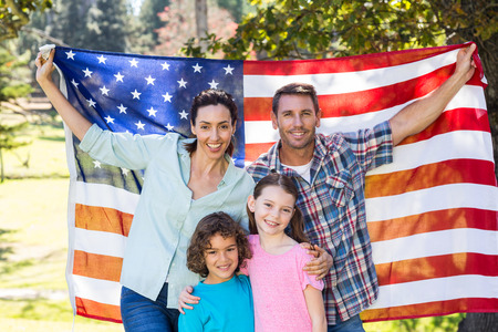 american flags: Familia feliz y sonriente con una bandera americana en un parque en un d�a soleado Foto de archivo