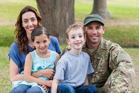 familia abrazo: Apuesto soldado reunirse con la familia en un día soleado