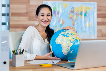 travel agent: Pretty travel agent holding globe and smiling at camera in the office