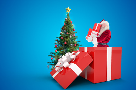 Santa standing in large gift against christmas tree