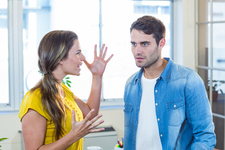 young adult woman: Casual business team having an argument in the office