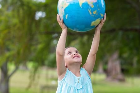 planeta tierra feliz: Niña que sostiene un globo en un día soleado Foto de archivo