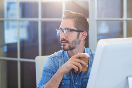 hip: Casual businessman sitting at desk and holding coffee in the office Stock Photo
