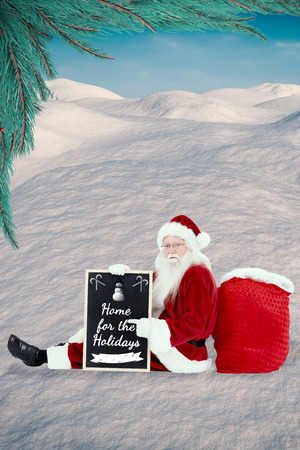 land scape: Santa sits leaned on his bag with a board against digitally generated snowy land scape