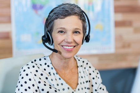 agents: Smiling travel agent sitting at her desk in the office