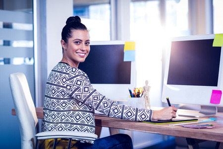 artistas: Feliz diseñador sonriendo a la cámara en la oficina creativa