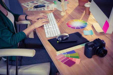 Designer pracuje u stolu v kanceláři tvůrčím