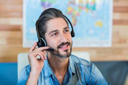travel agent: Smiling travel agent having phone call in the office