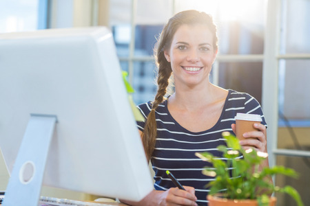 digitizer: Smiling casual businesswoman working on digitizer and holding coffee in the office