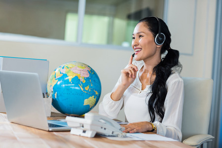 computer support: Pretty travel agent speaking to customer in the office