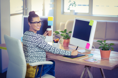 young adult women: Happy designer smiling at camera in creative office
