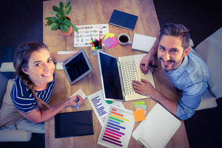 business graphics: Happy creative workers sharing desk in creative office