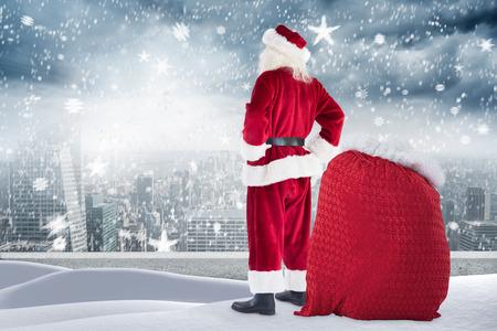ledge: Santa standing on snowy ledge against balcony overlooking city Stock Photo