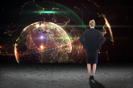 tied hair: Businesswoman standing with hands on hips against glowing lights surrounding earth
