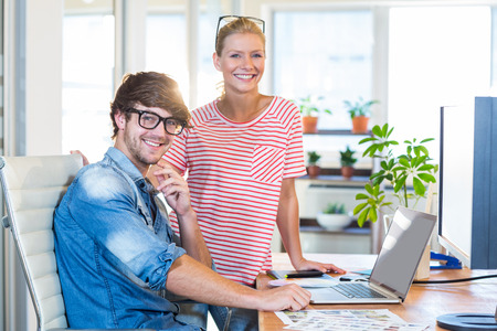 young man smiling: Smiling colleagues looking at camera in the office Stock Photo