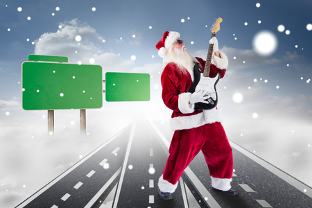 lean back: Santa playing electric guitar against roads over clouds with empty signposts Stock Photo