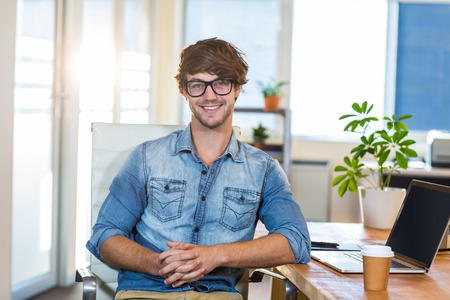 Smiling casual businessman sitting at desk in the office