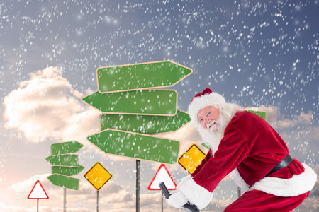 home trainer: Santa uses a home trainer against group of empty signposts Stock Photo