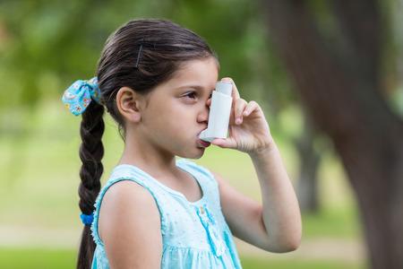 inhaler: Little girl using his inhaler on a sunny day Stock Photo