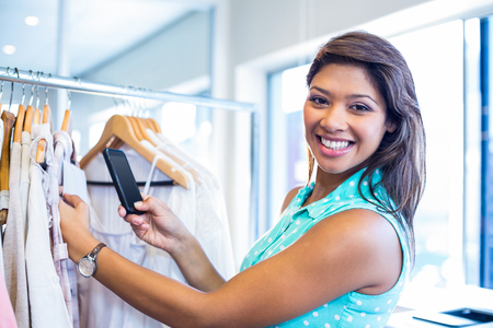 bar code scanner: Beautiful brunette scanning bar code with her mobile phone in clothes store Stock Photo