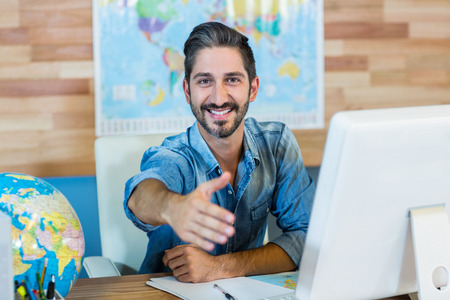travel agent: Smiling travel agent presenting his hand in the office
