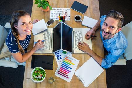 Lächelnde Partner arbeitet am Schreibtisch mit Laptop im Büro