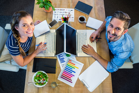 career women: Smiling partners working at desk using laptop in the office